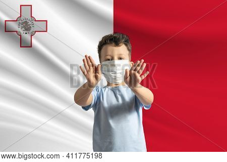 Little White Boy In A Protective Mask On The Background Of The Flag Of Malta. Makes A Stop Sign With