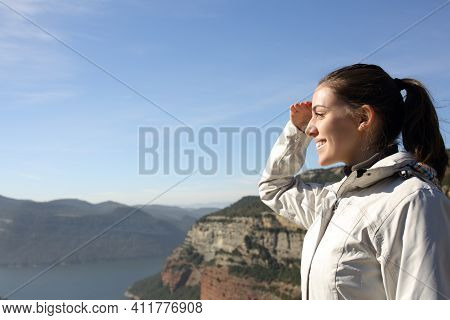 Side View Portrait Of A Happy Trekker Contemplating Views With Hand On Forehead In The Mountain On V