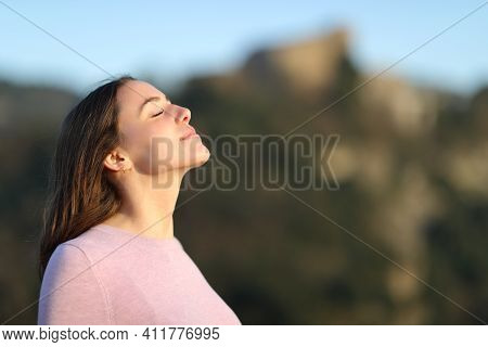 Relaxed Lady Breathing Fresh Air In The Mountainwith A Warm Light