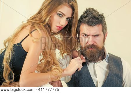 Woman With Razor, Scissors Cut Hair Of Man. Bearded Man And Sexy Woman With Long Curly Hair. Couple
