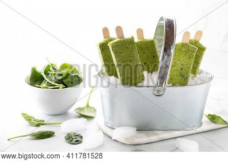 Close Up View Of Green Smoothie Popsicles In A Tin Pail Filled With Ice And Small Bowl Of Spinach Le