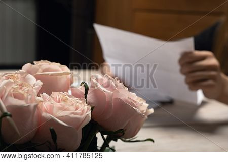Handwritten Letter In Human Hand Shot With Focus On Pink Rose Flower Bouquet