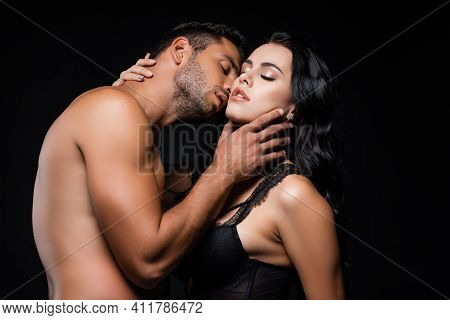 Shirtless Man Touching Neck And Kissing Sexy Woman Isolated On Black.