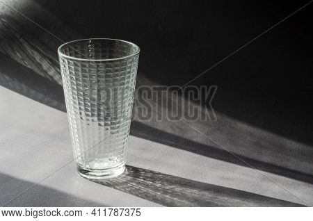 Empty Glass Beaker On A Gray Surface With Shadows. Transparent Glass With A Checkered Pattern. Abstr