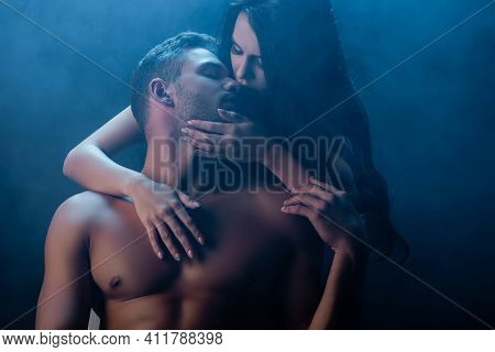 Passionate Woman Touching And Kissing Muscular Boyfriend With Closed Eyes On Black Background With S