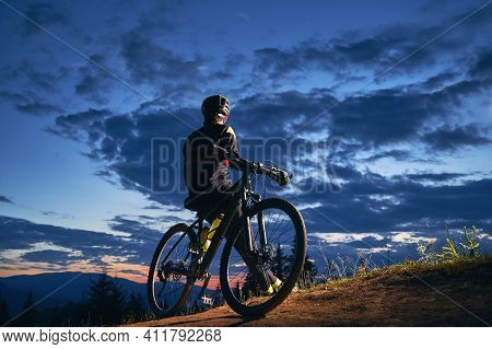 Back View Of Young Man In Cycling Suit Sitting On Bicycle Under Beautiful Night Sky. Male Bicyclist