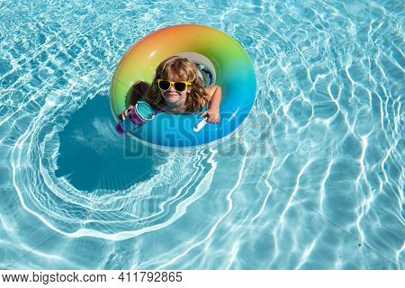 Playful Summer Kid At Beach With Rubber Circle. Summertime Activities Or Adventure At Aquapark. Chil