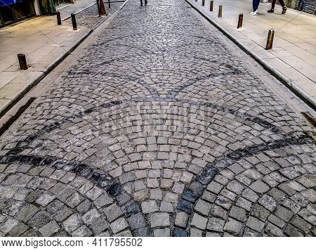 The Road Is Paved With Natural Granite Stone With An Arched Pattern. Laying Paving Slabs In The Old