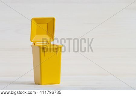 Empty Yellow Container For Sorting Garbage, With The Lid Open, Close-up On A White Wooden Background