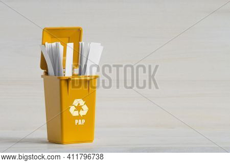 Yellow Container, For Sorting Garbage, With An Open Lid, White Paper, Ecology Icon, Close-up On A Wh