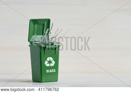 Green Container For Sorting Garbage, With An Open Lid, Glass Ampoules And An Ecology Icon. Close-up,