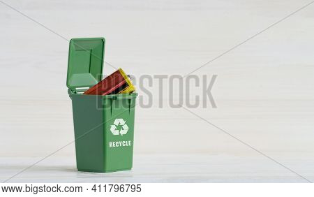 Green Garbage Sorting Container, With An Open Lid, Batteries, And An Ecology Icon. Close-up, White W