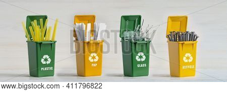 Four Plastic Dumpsters, Yellow And Green, With Sorted Garbage, Ecology Icon, On A White Isolated Bac