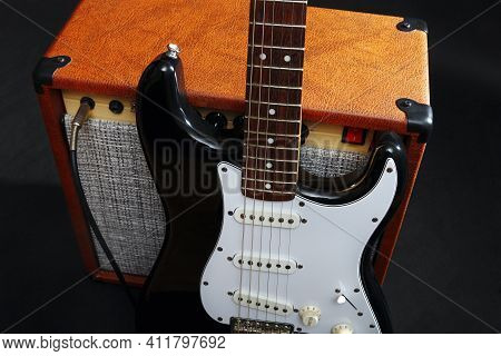 Guitar Combo Amplifier With Black Guitar On The Black Background.