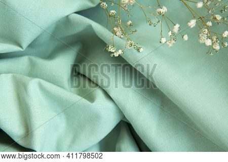 Draped Beautiful Folds Of Green Natural Fabric Background With Shadows And White Gypsophila Flowers.