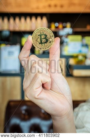 Close Up Of Someone Hand Showing Golden Bitcoin. Bitcoin Is One Of The Popular Cryptocurrency, A New