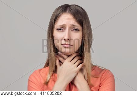 Throat Pain. Young Blond Woman Holding Her Inflamed Throat. Portrait Of Woman Suffering From Cold, F