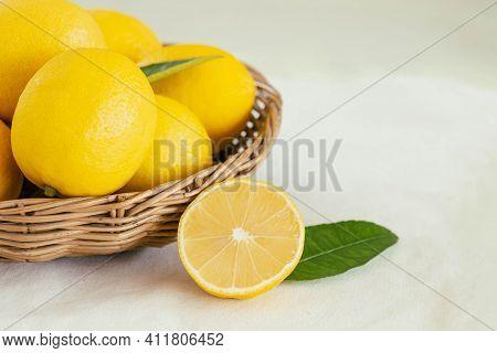 Group Of Whole And Cut Organic Lemon In Wood Basket On White Background. Fresh Lemon Have High Vitam