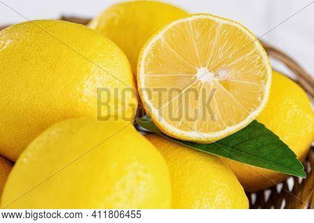 Close Up Group Of Whole And Cut Organic Lemon In Wood Basket On White Background. Fresh Lemon Have H