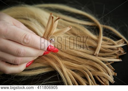 Encapsulated Strands Of Blonde Hair In Womens Hands With A Bright Red Manicure. The Concept Of Hair