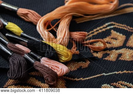 Multicolored Skeins With Floss Threads Scattered On Black Canvas Covered With Cross Stitch Pattern S