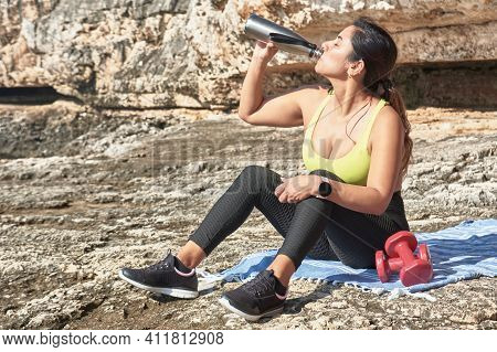 Seated Woman, Wearing Sports Clothes, Drinking Water From A Thermal Bottle, Next To A Pair Of Dumbbe