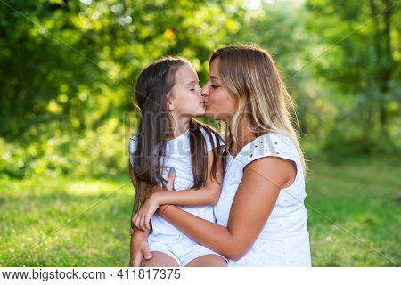 Little girl hugs kissing her mother in summer forest nature outdoor. Family, trust, kindness, maternity, parenthood, confidence, mother's love concept.