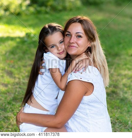 Little girl hugs her mother in summer forest nature outdoor. Family walks barefooted in park. Trust, kindness, maternity, parenthood, confidence, mother's love concept.