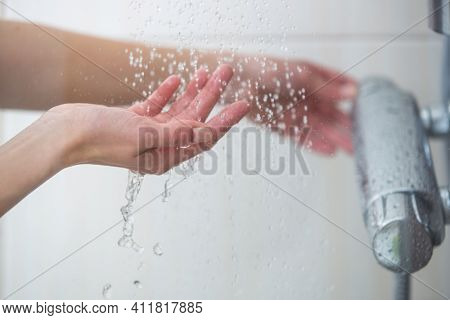 Woman taking a shower at home - female hands tryimg the temperature of water in shower