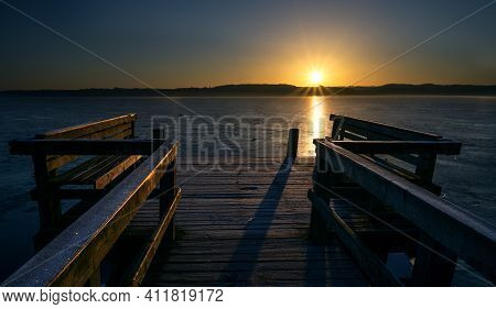 Wooden Jetty With Benches On A Frozen Lake In The Light Of The Golden Rising Sun, Beautiful Landscap