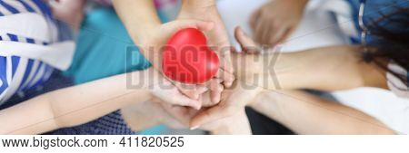Hands Of Adults And Children Hold Red Heart In Middle. Love And Health In Families Concept