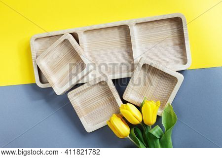 Wood Empty Plates For Snack And Flowers On Color Grey And Yellow Background