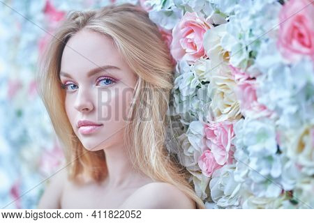Beautiful young woman with light makeup in pink colors and blonde hair on a background of blooming roses. Spring girl. Beauty concept.