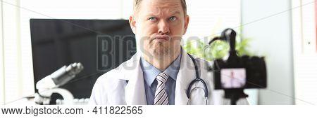 Portrait Of Thoughtful Doctor Recording Video In Video-blog. Popular Blogger Speaking To Followers A