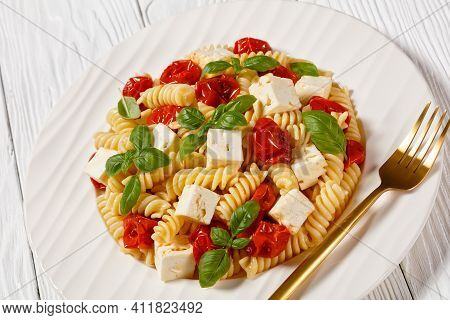 Baked Feta Cheese Fusilli Pasta With Cherry Tomatoes And Basil On A White Plate On A Wooden Table, I