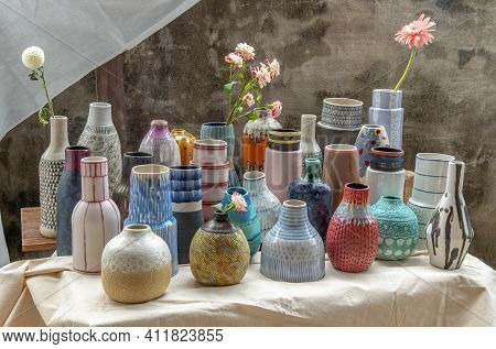 Bouquet Of Flowers In Handmade Assorted Many Different Ceramic Vases On Calico Textured Table Cloth