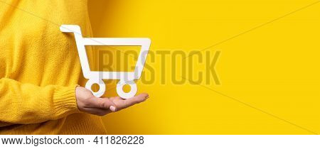 Shopping Cart On Hand Over Yellow Background, Panoramic Image, Buying Online Concept