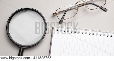 Business Summary Reports And A Magnifying Glass With Glasses On Table Office. Concept Of Data Analys