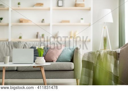 Modern Design Of Cozy Interior In Minimalist Style. Gray Sofa With Pillows, Table With Laptop And Fl