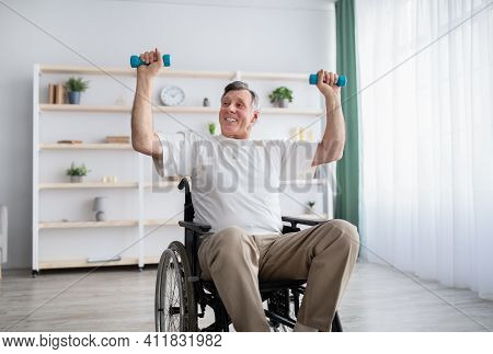 Physical Activities For Disabled Elderly Adults. Happy Handicapped Man In Wheelchair Making Rehabili