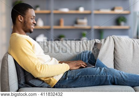 Side View Of Black Man Reclining On Couch In Living Room, Using Newest Laptop, Copy Space. Happy Afr