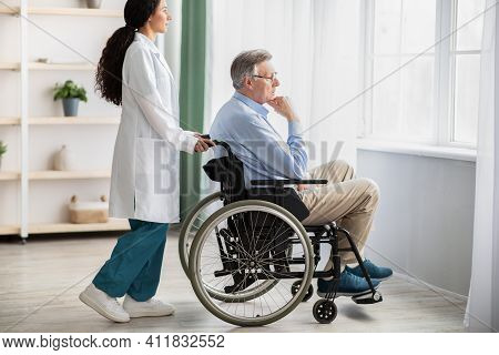 Side View Of Young Doctor Helping Elderly Disabled Man In Wheelchair, Indoors. Nurse Taking Care Of
