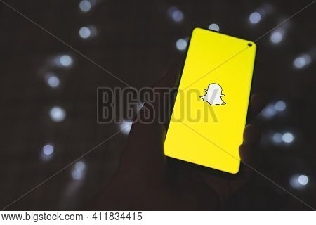 Man Holding A Smarphone With Snapchat App Yellow Logo On Dark Background