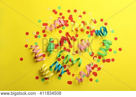 Colorful Serpentine Streamers And Confetti On Yellow Background, Flat Lay