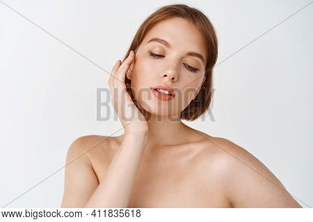 Skin Care And Women Beauty. Gentle Young Woman Naked Shoulders, Touching Natural Facial Skin Without