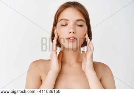 Beauty Face. Young Woman Rubbing Creme In Cheeks. Girl With Healthy Hydrated Facial Skin, Close Eyes