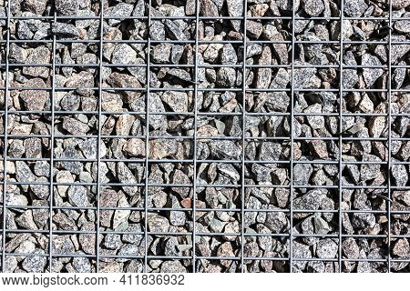 Gabion Made Of Black Stone And Metal Wire Mesh. A Stone Wall That Uses Metal And Stone In Harmony. E