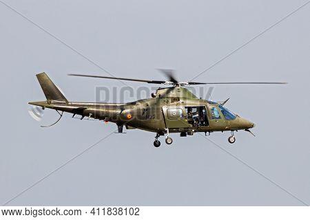 Belgian Air Force Agusta A109 Helicopter With Door Gunner In Flight Over Kleine Brogel Air Base. Bel