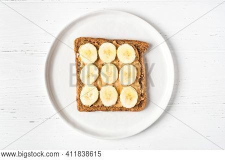 Homemade Peanut Butter Sandwich With Bananas And Honey On Wooden Background.