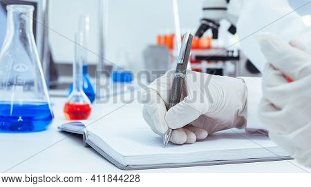Close Up. A Scientist Making An Entry In A Laboratory Journal.
